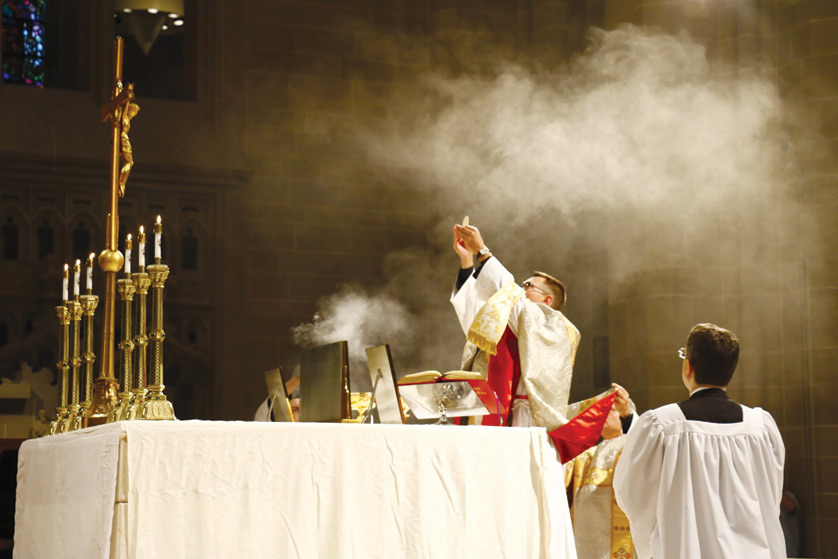 Fr. Clint McDonell elevates the host during a traditional Latin Mass on July 31 at the Cathedral of the Most Blessed Sacrament in Detroit. The Mass, during which Archbishop Allen H. Vigneron gave the homily, was the second hosted at the cathedral by the burgeoning young adult group Juventutem.